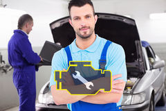 Composite image of male handyman standing arms crossed. Male handyman standing arms crossed against mechanic typing on a computer next to a car Royalty Free Stock Photos