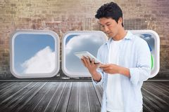 Composite image of male looking at his tablet computer Royalty Free Stock Images