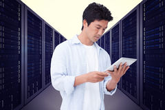 Composite image of male looking at his tablet computer Royalty Free Stock Photos