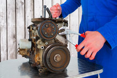 Composite image of male mechanic repairing car engine Royalty Free Stock Images