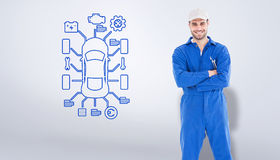 Composite image of male mechanic standing arms crossed on white background Stock Image