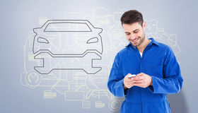 Composite image of male mechanic text messaging through mobile phone Royalty Free Stock Image