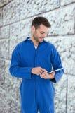Composite image of male mechanic using digital tablet. Male mechanic using digital tablet against grey brick wall Stock Image