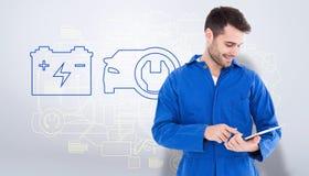 Composite image of male mechanic using digital tablet. Male mechanic using digital tablet against grey vignette Royalty Free Stock Image