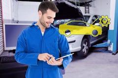 Composite image of male mechanic using digital tablet. Male mechanic using digital tablet against workshop Stock Image