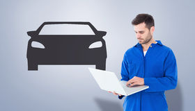 Composite image of male mechanic using laptop Royalty Free Stock Photography