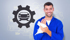 Composite image of male mechanic wiping hands with cloth. Male mechanic wiping hands with cloth against grey vignette Stock Photos