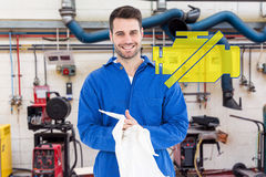 Composite image of male mechanic wiping hands with cloth Royalty Free Stock Photo