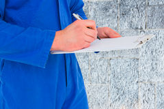 Composite image of male mechanic writing on clipboard. Male mechanic writing on clipboard against grey Stock Photo