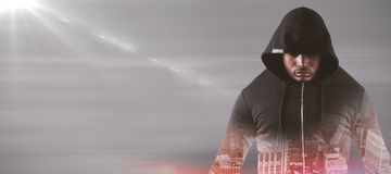 Composite image of male robber in black hoodie standing. Male robber in black hoodie standing against gray abstract image Royalty Free Stock Image