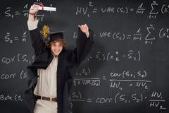 Composite image of male student in graduate robe jumping. Male student in graduate robe jumping against blackboard Stock Photos