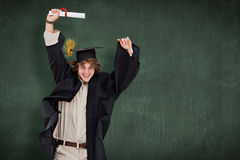 Composite image of male student in graduate robe jumping. Male student in graduate robe jumping against green chalkboard Stock Image