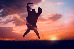 Composite image of male student in graduate robe jumping. Male student in graduate robe jumping against orange and blue sky with clouds Stock Photos