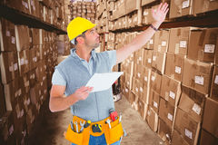 Composite image of male supervisor with hand raised holding clipboard. Male supervisor with hand raised holding clipboard against boxes in warehouse Stock Image