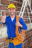 Composite image of male technician with wire roll gesturing thumbs up Royalty Free Stock Images