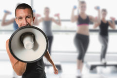 Composite image of male trainer yelling through megaphone Stock Photos