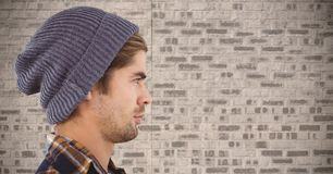 Composite image of Man with beanie against brick wall Stock Image