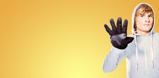 Composite image of man with black gloves staring at camera. Man with black gloves staring at camera against yellow vignette Stock Image