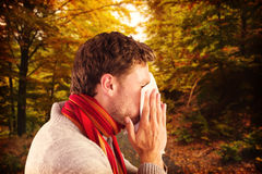 Composite image of man blowing nose on tissue. Man blowing nose on tissue against scenic shot of narrow road along forest Royalty Free Stock Images