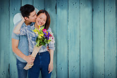 Composite image of man with bouquet kissing woman. Man with bouquet kissing woman against wooden planks Stock Photography