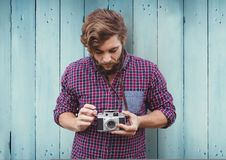 Composite image of Man with camera against blue wood panel Royalty Free Stock Photos