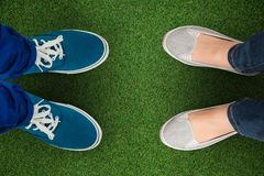 Composite image of man with canvas shoes on hardwood floor. Man with canvas shoes on hardwood floor against close up view of astro turf Royalty Free Stock Image