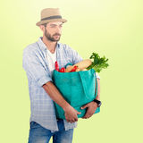Composite image of man carrying vegetables in shopping bag against white background Stock Images