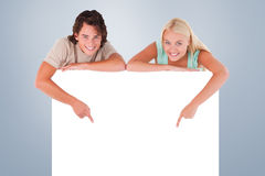 Composite image of man and cute woman pointing on a whiteboard Stock Images