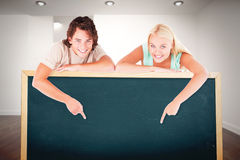 Composite image of man and cute woman pointing on a whiteboard. Man and cute women pointing on a whiteboard against white room with stairs Royalty Free Stock Photography