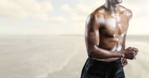 Composite image of man Fitness Torso against sea in background Stock Image