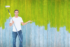 Composite image of man gesturing while holding paint roller Stock Image