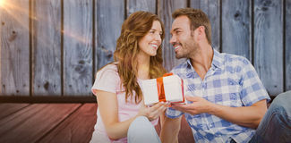 Composite image of man giving gift to woman Royalty Free Stock Photos