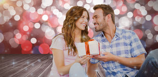 Composite image of man giving gift to woman Stock Image