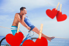 Composite image of man giving girlfriend a lift on his crossbar Royalty Free Stock Photography