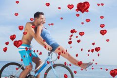 Composite image of man giving girlfriend a lift on his crossbar Stock Image