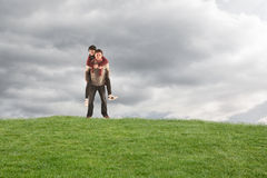 Composite image of man giving girlfriend piggy back Royalty Free Stock Photo