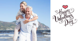 Composite image of man giving his laughing wife a piggy back at the beach Stock Image