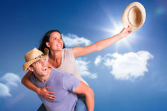 Composite image of man giving his pretty girlfriend a piggy back. Man giving his pretty girlfriend a piggy back against bright blue sky with clouds Royalty Free Stock Images