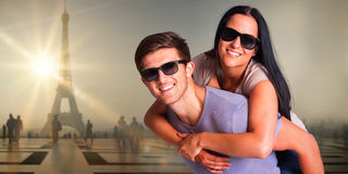 Composite image of man giving his pretty girlfriend a piggy back Royalty Free Stock Photos