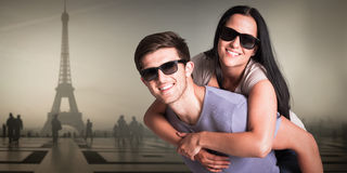 Composite image of man giving his pretty girlfriend a piggy back Royalty Free Stock Photo
