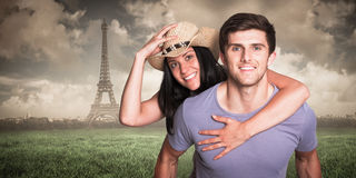 Composite image of man giving his pretty girlfriend a piggy back. Man giving his pretty girlfriend a piggy back against paris under cloudy sky Royalty Free Stock Image