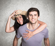 Composite image of man giving his pretty girlfriend a piggy back Stock Images