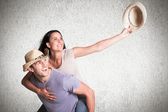 Composite image of man giving his pretty girlfriend a piggy back Royalty Free Stock Image