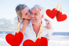 Composite image of man giving his smiling wife a piggy back at the beach Stock Photos