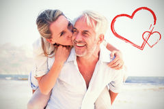 Composite image of man giving his smiling wife a piggy back at the beach Royalty Free Stock Photography