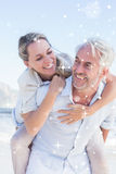 Composite image of man giving his smiling wife a piggy back at the beach Stock Photography