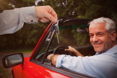 Composite image of man giving keys to someone. Man giving keys to someone against smiling man driving red car Stock Photography