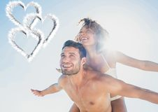 Composite image of man giving piggy back to woman Stock Photos