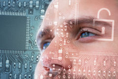 Composite image of man with green eyes. Man with green eyes against lock in circuit board Royalty Free Stock Photo