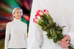 Composite image of man hiding bouquet of roses from older woman Stock Photography
